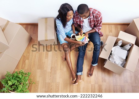 overhead view of young black african couple with moving boxes in new apartment choosing colour of paint for walls - stock photo