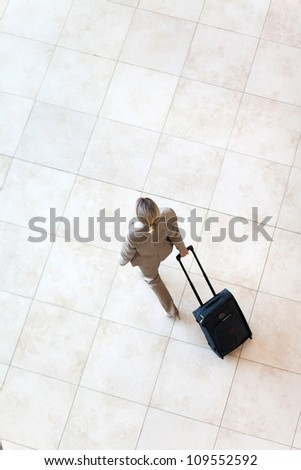 overhead view of young businesswoman walking at airport - stock photo