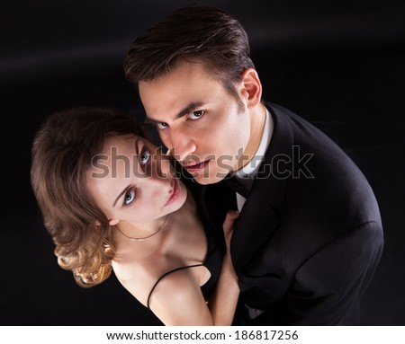 Overhead view of young couple kissing isolated over black background - stock photo