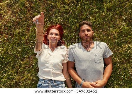 Overhead view of young man and woman lying on the grass, with woman pointing at something interesting. Top view of relaxed young couple lying down on meadow. - stock photo