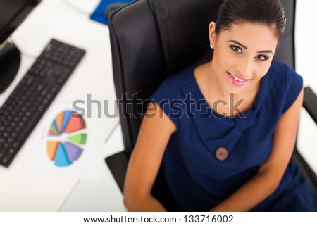 overhead view of young office worker sitting in her office - stock photo