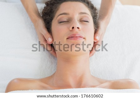 Overhead view of young woman receiving massage in health spa - stock photo