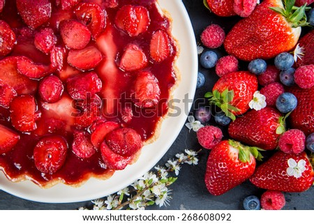 overhead view on fresh strawberry pie with berries fruit on side and flowers - stock photo