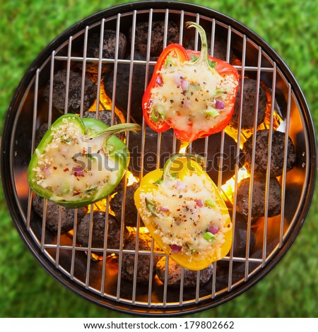 Overhead view on green grass of grilling stuffed savory bell peppers topped with melted cheese over the fire on an outdoor summer BBQ or picnic - stock photo