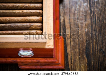 Overhead view on humidor with cigars, on wooden table. Tabacconist or cigar collector concept. - stock photo