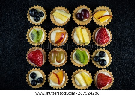 Overhead view on mini party tartlets with fresh fruit, on black slate background - stock photo