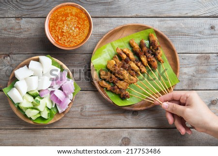Overhead view people holding chicken satay on wooden dining table, one of famous local dishes. - stock photo