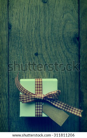 Overhead white box on old wood plank table, tied to a bow in red and cream gingham ribbon, with vintage effect parchment style label left blank for copy space.  Cross processed for retro appearance. - stock photo
