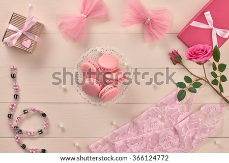 Overhead woman essentials fashion wedding accessories set. Lace gloves, macarons, gift boxes, necklace and roses. Creative bride set, vanilla wooden background. Romantic modern, still life. Top view - stock photo