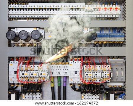 Overloaded electrical circuit causing electrical short and fire. - stock photo