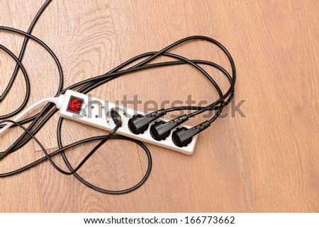 Overloaded power board, on wooden floor background - stock photo