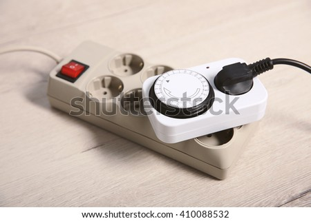 Overloaded power board on wooden floor background - stock photo