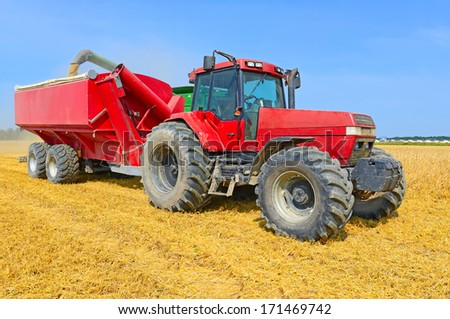 Overloading grain harvester into the grain tank of the tractor trailer - stock photo