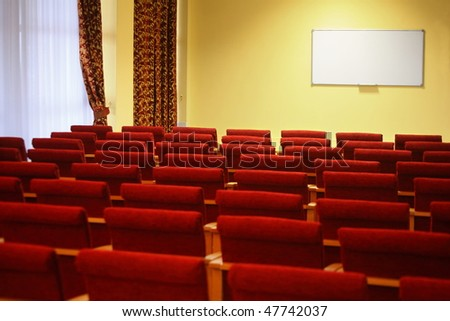 overlook of empty conference hall. rows of a chairs. window in a left side of image. focus on a screen