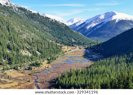 overlook of the snow covered mountains, trees and mountain creek in Colorado from above - stock photo