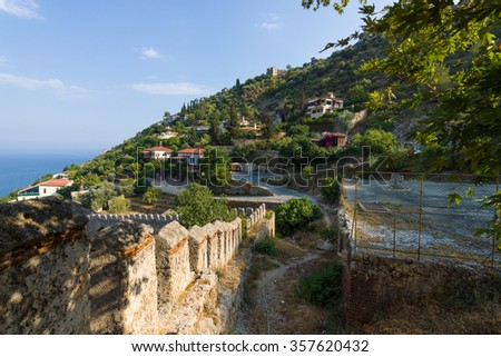 Overlooking the Mediterranean Sea and the edge of a hill with houses. in the foreground the ruins of an ancient fortress. Alanya. Turkey. - stock photo