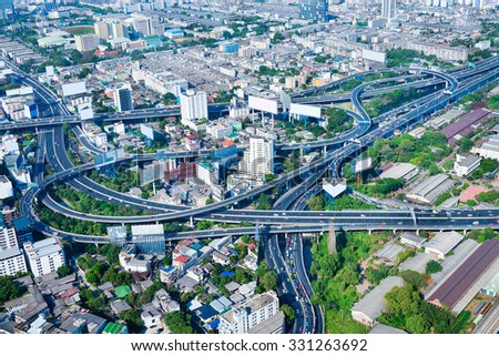 Overlooking view of Bangkok's modern cityscape with a complex highway interchange snaking around tall buildings and lush, green trees. - stock photo