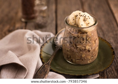 Overnight oats with chia seeds and banana on old wood table
