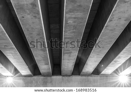 Overpass seen from below showing support beams in black and white - stock photo
