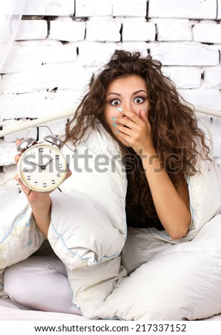 Oversleeping girl with alarm clock in the bed under  quilt on modern wall background - stock photo