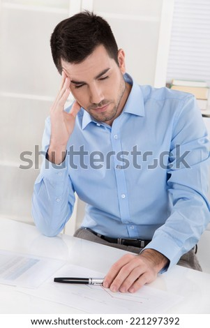 Overstrained and overworked businessman with headache: Portrait sitting in his office. - stock photo