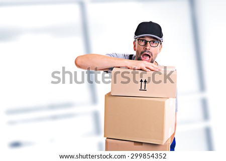 overstrained postman with parcels and dark cap - stock photo