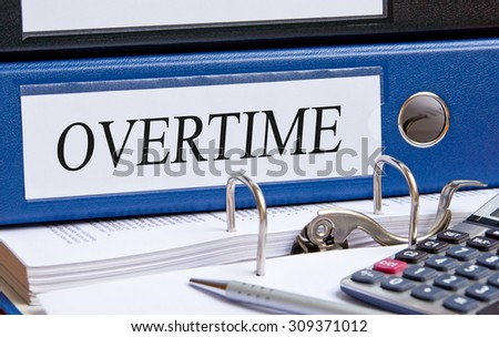 Overtime - blue binder in the office - stock photo