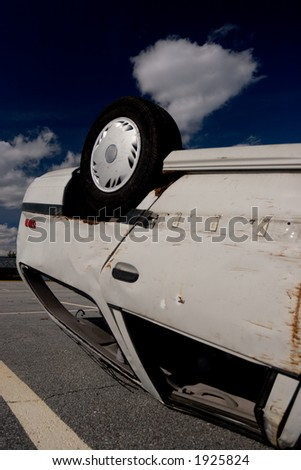 Overturned car on a parking lot, rear wheel shown - stock photo