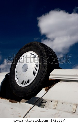 Overturned car, wheel in the air, against deep sky