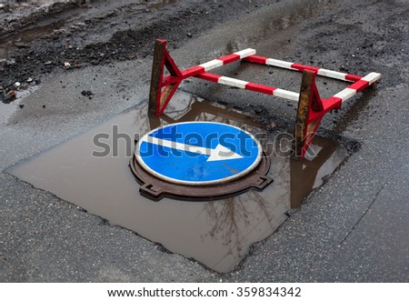 Overturned construction safety barrier and turn right sign in the puddle on the road. The sign is on the manhole cover  inside the cut out part of asphalt surface prepared for paving with new asphalt. - stock photo