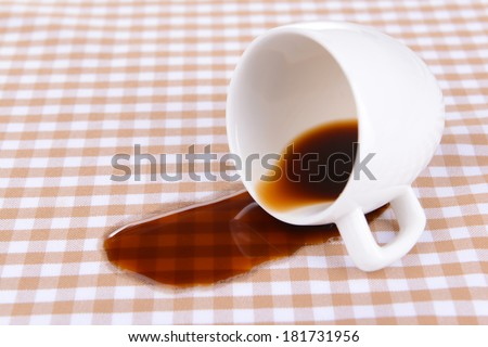 Overturned cup of coffee on table close-up - stock photo