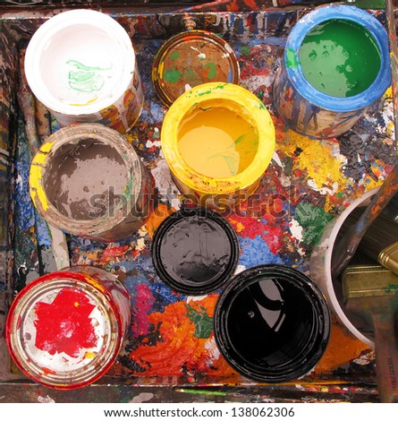 overview of open paint cans in spattered paint box - stock photo