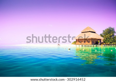Overwater bungalows on the tropical island resort of Maldives at night.  Scenic sunset over the Ocean. - stock photo