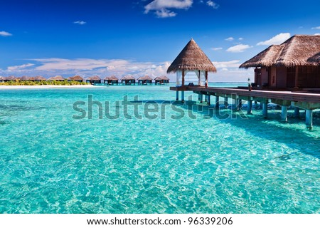 Overwater spa in blue lagoon around tropical island - stock photo