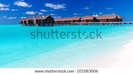 Overwater villas in blue tropical lagoon with white sandy beach - stock photo