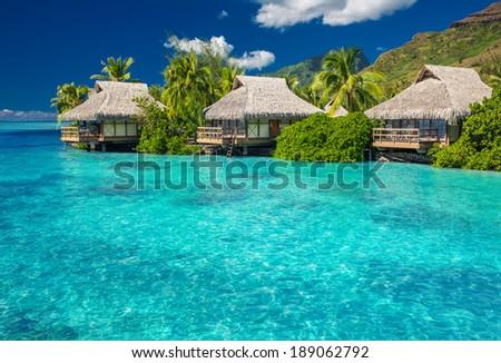 Overwater villas in tropical lagoon of Moorea Island - stock photo