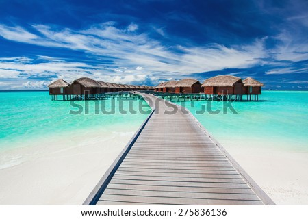 Overwater villas on the tropical lagoon connected to island by jetty - stock photo