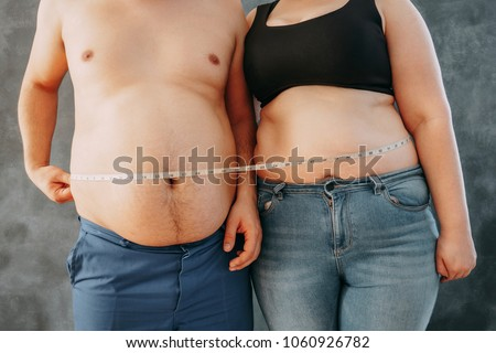 Overweight couple standing together wrapped with measure tape. Dieting, family weight losing and health care concept