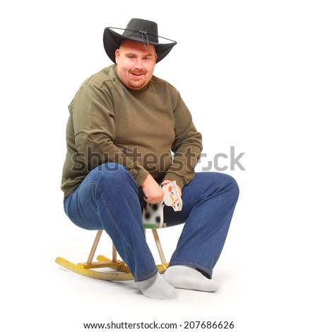 Overweight cowboy riding on a rocking horse. - stock photo