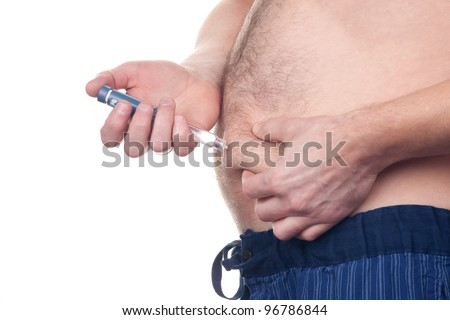 Overweight fat man with diabetes gets an insulin injection in abdomen area over white background. - stock photo