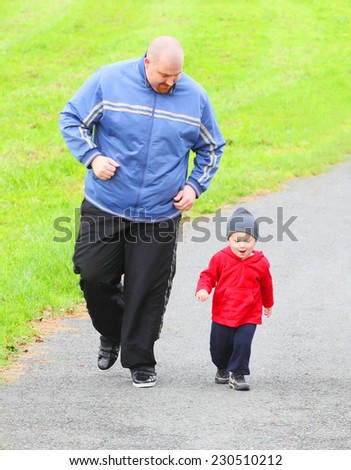Overweight father with her son running together. - stock photo