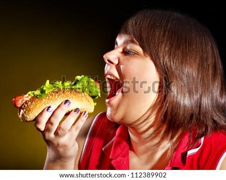 Overweight hungry woman eating hamburger. - stock photo