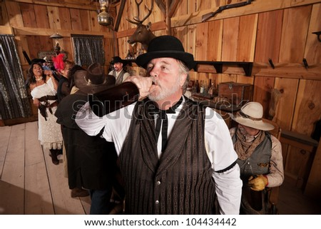 Overweight man drinks from a bottle of alcohol in a saloon - stock photo