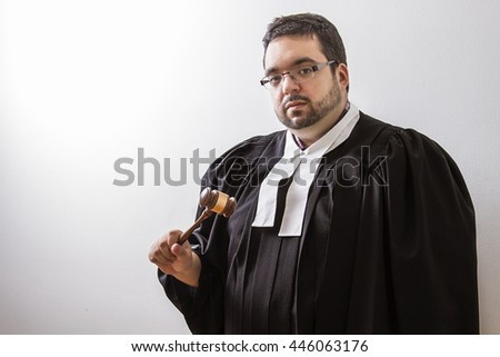 Overweight man in canadian lawyer toga, with a gavel in his hand - stock photo