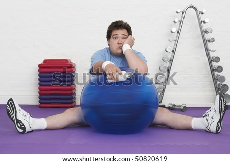 Overweight Man sitting on floor with exercise ball in health club, portrait - stock photo