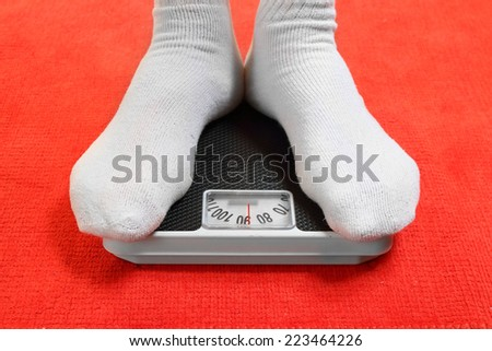 Overweight man standing on a retro style weighing machine  - stock photo