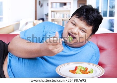Overweight man try to diet by eating vegetable at home - stock photo