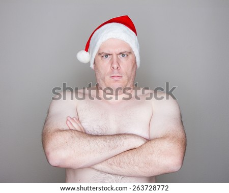 Overweight man wearing a santa hat looking at the camera firm - stock photo