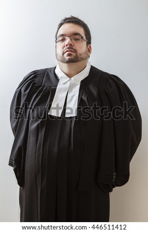 Overweight man, with arms behind his back, in canadian lawyer toga against a white background - stock photo