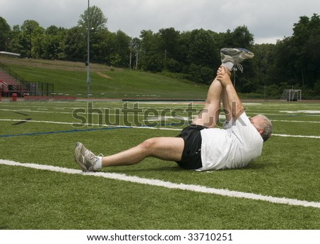 overweight middle age retired and active senior man stretching his leg muscles after exercising on a sports field outdoors - stock photo